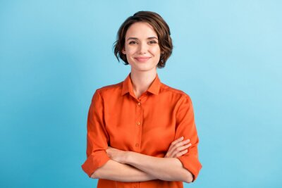 Naklejka Photo of attractive charming lady cute bobbed hairdo arms crossed self-confident person worker friendly smile good mood wear orange office shirt isolated blue color background