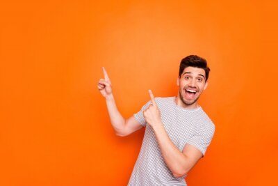 Naklejka Photo of attractive guy hold hands fingers direct up empty space excited good mood sales person wear striped t-shirt isolated bright orange color background