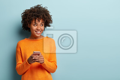 Naklejka Photo of cheerful delighted African American woman types sms on modern cell phone device, enjoys good internet connection, dressed in orange jumper, focused aside, isolated on blue studio wall