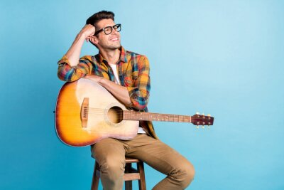 Naklejka Photo of funny dreamy young gentleman wear checkered shirt holding guitar looking empty space smiling isolated blue color background