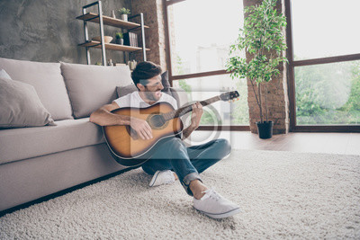 Naklejka Photo of mixed race guy sitting floor leaning sofa hold acoustic instrumental guitar playing new written song sound signing creative talented person flat loft living room indoors