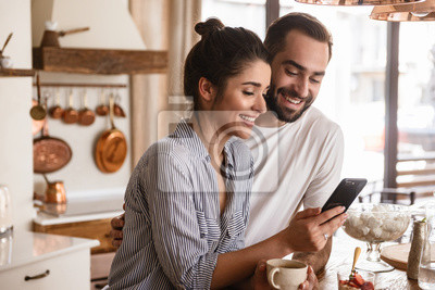 Naklejka Photo of smiling brunette couple drinking coffee and using cell phone during breakfast at home