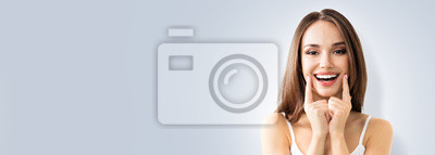 Naklejka Photo of young toothy smiling woman showing smile, over grey background