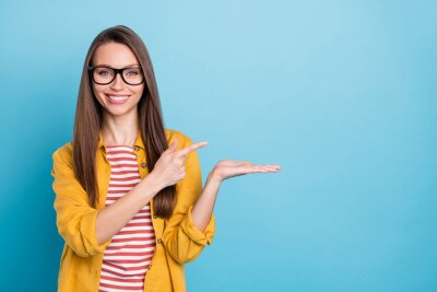 Naklejka Photo of young woman happy positive smile point finger product promo advert choice sale isolated over blue color background