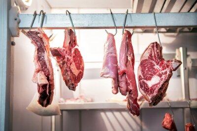Naklejka Pieces of fresh beef hanging in refrigerator