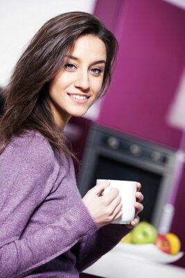 Piękna młoda kobieta kawie w kuchni, podczas gdy