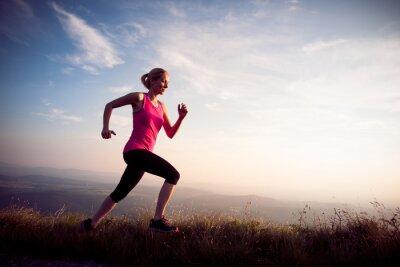 Naklejka piękna młoda kobieta runns cross country na mountian drogi na