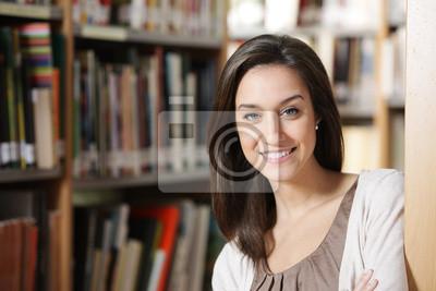 Piękna młoda kobieta, stojąca w bibliotece