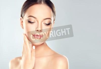 Naklejka Piękna młoda kobieta z Czystą świeżą skórą dotykać własnej twarzy. Zabieg na twarz . Kosmetologia, piękno i spa.