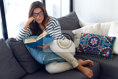 Naklejka Piękna młoda kobieta z książką na kanapie.