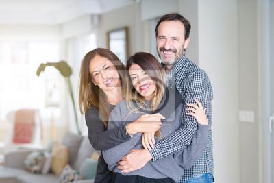 Naklejka Piękna rodzina razem. Matka, ojciec i córka uśmiecha się i ściska z miłością w domu.