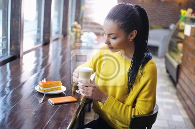 Naklejka Piękne rasy mieszanej nastoletnia dziewczyna korzystających z jej kawę z filiżanki latte i ciasto