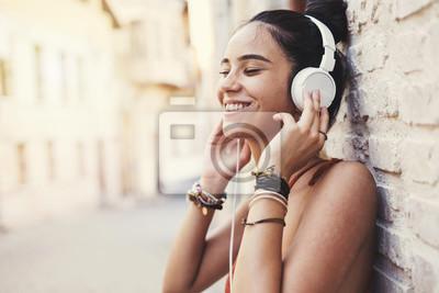 Naklejka Pięknej młodej dziewczyny słuchająca muzyka