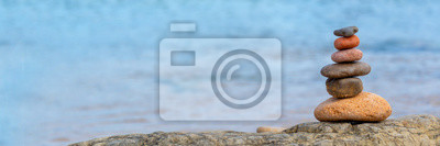 Naklejka Pile of pebbles on a beach, panoramic blue water background