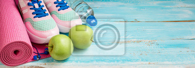 Naklejka Pink yoga mat, sport shoes, bottle of water and apples on blue wooden background. Sport, healthy lifestyle, yoga concept. Female sport equipment. Copy space