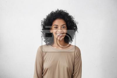 Naklejka Pionowe w górę Portret wesołej młodych wyścigu mieszanych żeński z kręcone włosy stwarzających w studio z uśmiechem szczęśliwy. Czarnowłosa kobieta ubierała się niechcenia uśmiechając się, pokazując b