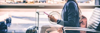 Naklejka Płaska pasażerska kobiety czekanie dla lota odjazdu texting sms wiadomość na telefonie komórkowym przy holu lotniskiem. Biznesmeni podróży styl życia panoramicznego sztandaru.