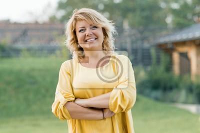Naklejka Plenerowy portret pozytywna ufna dojrzała kobieta. Uśmiechnięta żeńska blondynka w żółtej sukni z rękami krzyżował blisko domu