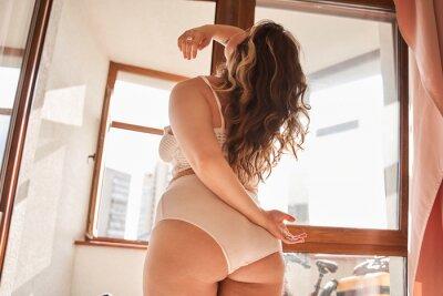 Naklejka Plus size woman wearing lingerie standing in front of the window