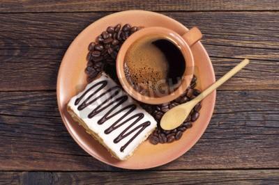 Naklejka Płytka z filiżanką gorącej kawy i kremowym ciasto na ciemnym drewnianym stole, widok z góry