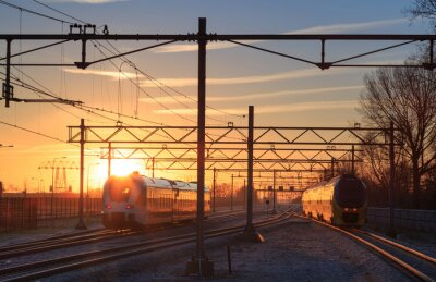 Naklejka Pociągi pozostawiając stację podczas wschodu słońca zimą.