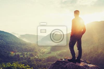Naklejka Podróżnik młody człowiek stojący w górach latem o zachodzie słońca i cieszyć widok natury