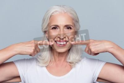 Naklejka Pojęcie o silne zdrowe proste białe zęby w starszym wieku. Zamyka w górę portreta szczęśliwy z promieniejącym uśmiechu żeńskim emerytem wskazuje na jej perfect jasnych białych zębach, odizolowywającyc