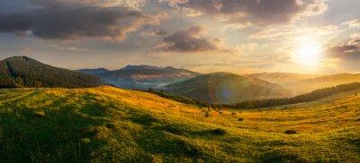 Naklejka pole rolne w górach na zachodzie słońca
