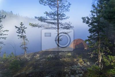 Naklejka Pomarańczowy namiot turystyczny przed zamglonym jeziorem. Karelia, Rosja.