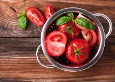 Naklejka Pomidory z bazylią w durszlak na drewnianym stole tle. Skład żywności. Widok z góry