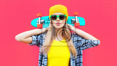 Naklejka Portrait cool woman with skateboard wearing colorful yellow hat on pink background