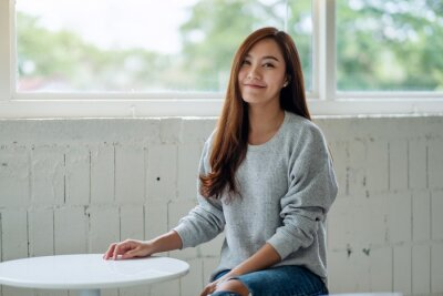 Naklejka Portrait image of a beautiful young asian woman sitting in cafe with feeling happy