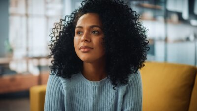 Naklejka Portrait of a Beautiful Authentic Latina Female with Afro Hair Wearing Light Blue Jumper and Glasses. She Looks Away and Thinking about Life. Successful Woman Resting in Bright Living Room.