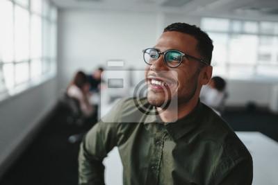 Naklejka Portrait of a handsome casual businessman wearing black eyeglasses in office smiling