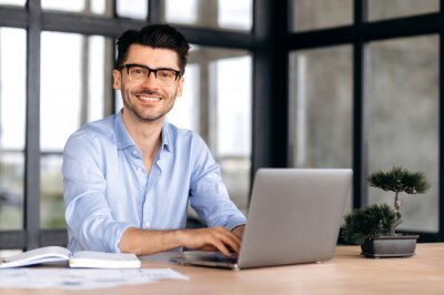 Naklejka Portrait of a handsome intelligent caucasian man with glasses, businessman or manager, in formal shirt, sitting at a table with laptop, looking at camera and smiling friendly