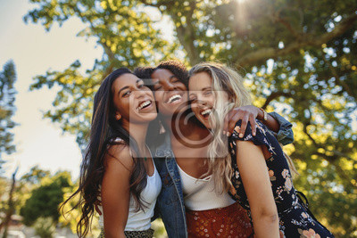 Naklejka Portrait of a happy multiethnic group of smiling female friends - women laughing and having fun in the park on a sunny day
