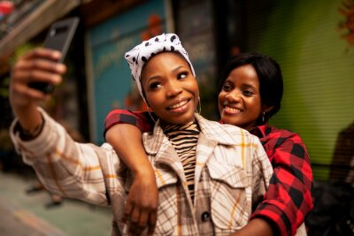 Naklejka Portrait of a happy smiling female friends. Beautiful happy girlfriends taking a selfie together