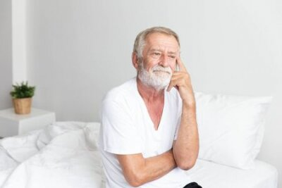 Naklejka Portrait of a senior retirement man sitting and thinking alone on bed in his home
