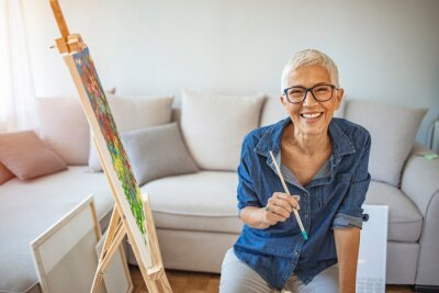 Naklejka Portrait of attractive middle aged professional female painter with gray hair working at home standing in front of easel. Happy mature woman painting and watching at camera.