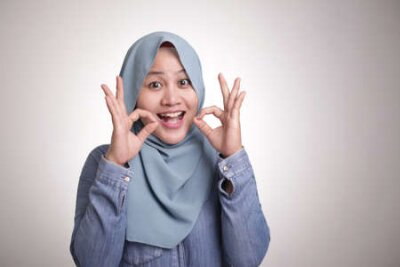 Naklejka Portrait of beautiful Asian muslim woman smiling while making delicious hand gesture with her fingers, isolated on white