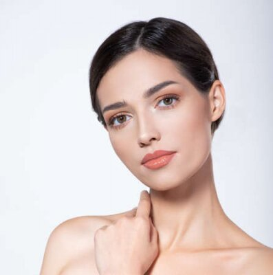 Naklejka Portrait of beautiful  brunette girl which touching her fresh face. Beautiful face of young woman with health fresh skin.  Beautiful face of young adult woman with clean fresh skin. Skin care.