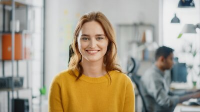 Naklejka Portrait of Beautiful Young Woman with Red Hair Wearing Yellow Sweater Smiling at Camera Charmingly. Successful Woman Working in Bright Diverse Office.