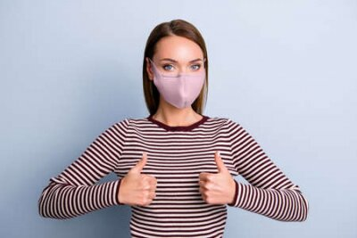 Naklejka Portrait of charming pretty girl in pink fabric face mask showing two thumbs up looking at camera isolated on grey background