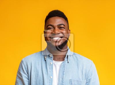 Naklejka Portrait of cheerful bearded black man over yellow background