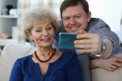 Naklejka Portrait of cheerful mother and son taking selfie to remember. Smiling elderly woman posing for picture on sofa at home. Family relationship and spare time concept