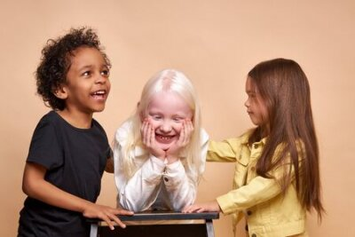 Naklejka portrait of cheerful positive kids, multiethnic children isolated in studio. adorable afro boy and albino, caucasian girls stand together, posing. international friendship