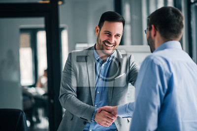 Naklejka Portrait of cheerful young manager handshake with new employee.