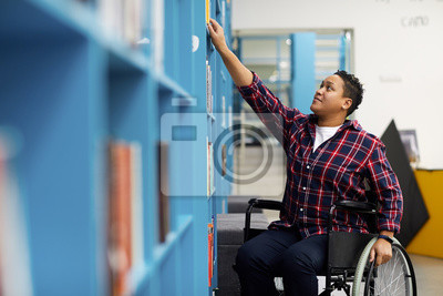 Naklejka Portrait of disabled student in wheelchair choosing books while studying in college library, copy space