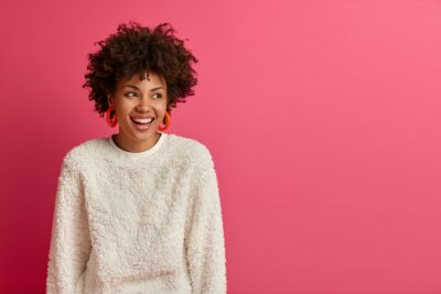 Naklejka Portrait of dreamy good looking woman with Afro hairstyle, looks away and laughs, discusses funny recent deal at work, has pleasant friendly talk, dressed in casual wear, isolated on pink wall