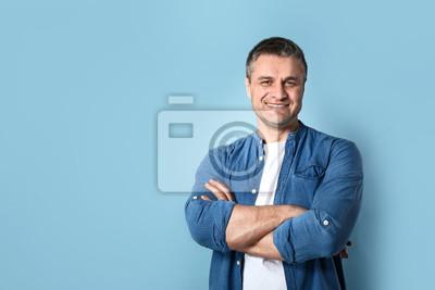 Naklejka Portrait of handsome mature man on color background